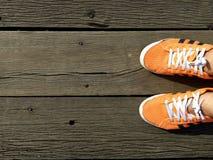 Draufsicht von den orange Turnschuhen des Mannes, die auf der Holzbrücke alt stehen lizenzfreies stockbild