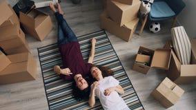 Draufsicht von den Paaren, die auf Boden in der neuen Wohnung spricht während der Verlegung liegen stock video footage