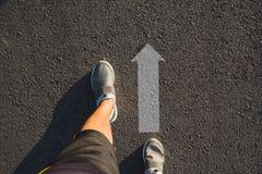 Draufsicht von den tragenden Schuhen des Mannes, die eine Weise markiert mit Pfeilen wählen lizenzfreie stockfotografie