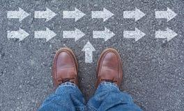 Draufsicht von den tragenden Schuhen des Mannes, die eine Weise markiert mit Pfeilen wählen stockbild