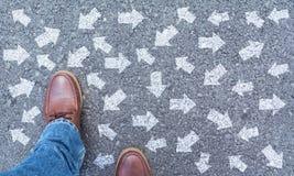 Draufsicht von den tragenden Schuhen des Mannes, die eine Weise markiert mit Pfeilen wählen lizenzfreie stockfotos