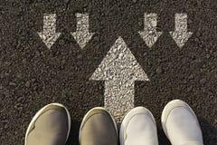 Draufsicht von den tragenden weißen Schuhen des Mannes, die eine Weise markiert mit weißen Pfeilen wählen Wählt das rechte Wegkon lizenzfreies stockbild