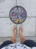 Draufsicht von den weiblichen Beinen, die Pantoffel vor einem farbigen Einsteigeloch in Matsumoto, Japan tragen stockbilder