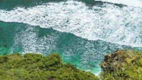 Draufsicht von den Wellen, die eins nach dem anderen zum Nunggalan-Strand, Uluwatu, Bali, Indonesien rollen stock video