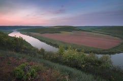 Draufsicht von Dnestr-Fluss bei Sonnenaufgang Fluss wird mit Nebel bedeckt und umgeben mit grünem Wald und Feldern Stockfotografie