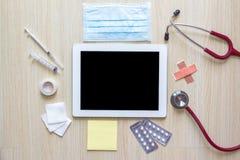 Draufsicht von Doktorschreibtisch mit Tablette und medizinischem Gerät Stockbilder