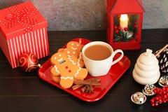 Draufsicht von drei Lebkuchenmännern mit Kaffee auf rotem Teller stockfoto