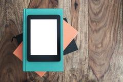 Draufsicht von eBook Leser auf Stapel Büchern auf Holztisch lizenzfreie stockfotos