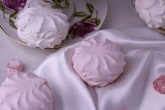 Draufsicht von Eibischen und von Bonbons, die auf einer Seide liegen, weißer Stoff stockfotografie