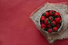 Draufsicht von Erdbeeren in der Schüssel auf rotem Hintergrundblumenstrauß von Pfingstrosen lizenzfreie stockbilder