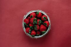 Draufsicht von Erdbeeren in der Schüssel auf rotem Hintergrundblumenstrauß von Pfingstrosen lizenzfreie stockfotografie