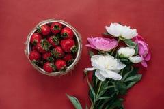 Draufsicht von Erdbeeren in der Schüssel auf rotem Hintergrundblumenstrauß von Pfingstrosen stockfoto