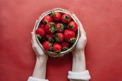 Draufsicht von Erdbeeren in der Schüssel auf rotem Hintergrundblumenstrauß von Pfingstrosen lizenzfreie stockfotos
