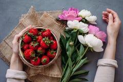 Draufsicht von Erdbeeren in der Schüssel auf rotem Hintergrundblumenstrauß von Pfingstrosen stockfotos