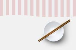 Draufsicht von Essstäbchen mit Schüssel auf weißem Hintergrund Lizenzfreie Stockfotografie