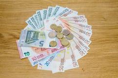 Draufsicht von Euromünzen und von Banknoten auf hölzernem Lizenzfreie Stockbilder