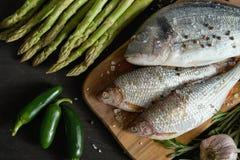 Draufsicht von frischen rohen dorada Fischen auf einem hölzernen Brett mit einem Satz Gemüse auf einer schwarzen Tabelle stockfoto