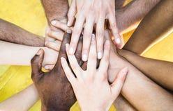 Draufsicht von gemischtrassigen stapelnden Händen - internationale Freundschaft stockfotografie