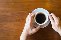 Draufsicht von Hand& x27; s-Manngriff ein Schale heißen Kaffee auf altem hölzernem ta Lizenzfreie Stockfotos