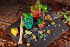 Draufsicht von hellen Sommercocktails mit Minze, Kalk, Eis, Beeren und Carambola auf dem hölzernen Hintergrund Kopieren Sie Platz Stockfoto