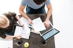 Draufsicht von jungen Paaren arbeiten mit Papieren und Laptop zu Hause Lizenzfreie Stockbilder