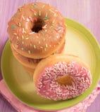 Draufsicht von köstlichen Schaumgummiringen mit Zuckerglasur auf grüner Platte Lizenzfreie Stockfotos