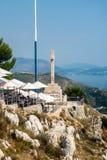Draufsicht von Leuten an einem Restaurant auf eine Gebirgsoberseite mit dem adriatischen Meer im Hintergrund lizenzfreies stockfoto