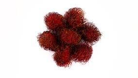 Draufsicht von oben eines Haufens der rote Farberambutanfrüchte Langsam, drehend auf die Drehscheibe lokalisiert auf dem Weiß stock video footage