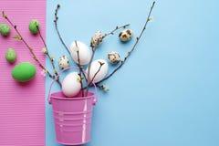 Draufsicht von Ostereiern mit den Frühlingsgrünzweigen und dekorativem rosa Eimer auf einem rosa-blauen Pastellhintergrund Lizenzfreie Stockfotografie