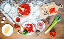 Draufsicht von Pizzabestandteilen, -tomaten, -salami und -pilzen Lizenzfreie Stockfotografie