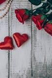 Draufsicht von Rosen, von Geschenkbox mit Perle und von zwei roten Herzen auf hölzernem Hintergrund Stockbild
