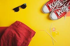 Draufsicht von roten Turnschuhen, von roten kurzen Hosen und von Sonnenbrille auf gelbem Hintergrund lizenzfreies stockfoto