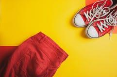 Draufsicht von roten Turnschuhen und von roten kurzen Hosen auf gelbem Hintergrund stockfoto