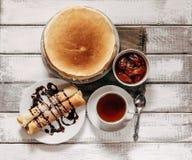 Draufsicht von selbst gemachten Pfannkuchen oder von Blini mit Schokoladencreme, Schale schwarzer Tee Stockbild