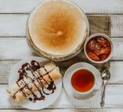 Draufsicht von selbst gemachten Pfannkuchen oder von Blini mit Schokoladencreme, Schale schwarzer Tee Lizenzfreie Stockfotos