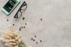 Draufsicht von Smartphone mit Anmeldung App auf Schirm mit Brillen verschüttete Kaffeebohnen und lagurus ovatus Blumenstrauß stockfotografie