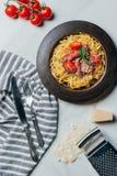 Draufsicht von Teigwaren mit tadellosen Blättern, jamon und den Kirschtomaten bedeckt durch Parmesankäse auf Platte am Marmortisc lizenzfreie stockfotografie