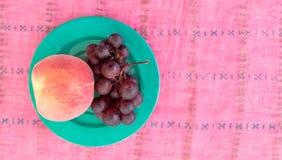 Draufsicht von Trauben mit Pfirsich in einer Platte Stockbilder