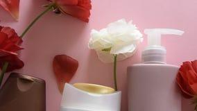 Draufsicht von verschiedenen hygienischen/kosmetischen Produkten und von Blumen auf neuem rosa Hintergrund Wellnessschönheitsbeh stock video