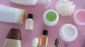 Draufsicht von verschiedenen hygienischen/kosmetischen Produkten und von Blumen auf neuem rosa Hintergrund Wellnessschönheitsbeh stock footage