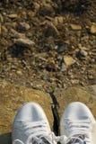 Draufsicht von weißen Turnschuhen auf einem Gebirgsfelsen stockfotografie