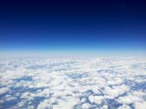 Draufsicht von weißen Wolken von einem Flugzeug, auf einem Hintergrund des klaren blauen Himmels Stockbilder