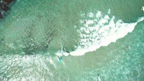Draufsicht von Wellen brechen auf tropischem weißem Sandstrand und -Surfer mit surfendem Brett Luftbrummenansicht 4k schoss vom M stock footage