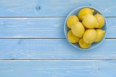 Draufsicht von Zitronen auf blauer Platte über tropischem Hintergrund Stockfotos