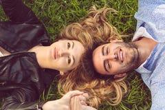 Draufsicht von zwei Freunden, die beim Blicken in Richtung des Himmels wie sie legend am Gras lächeln Stockbilder