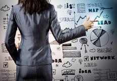 Draufsicht von zwei Geschäftsmännern, die etwas während einer von ihnen die Diagramme auf dem Papier zeigend dicussing sind Stockfotos
