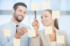 Draufsicht von zwei Geschäftsmännern, die etwas während einer von ihnen die Diagramme auf dem Papier zeigend dicussing sind Stockbilder