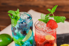 Draufsicht von zwei hellen alkoholischen Cocktails mit Minze, Kalk, Eis, Erdbeeren auf dem hölzernen Hintergrund Sommergetränke Lizenzfreies Stockfoto