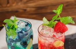 Draufsicht von zwei hellen Cocktails mit Minze, Eis, Beeren auf dem hölzernen Hintergrund Sommerbonbongetränke Alkoholische Cockt Lizenzfreie Stockfotos