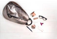 Draufsicht zu den Frauen silberner Rucksack und Zusätze auf weißem Hintergrund Weiblicher Artblick Geburtstagsfeier des Valentins lizenzfreie stockfotografie